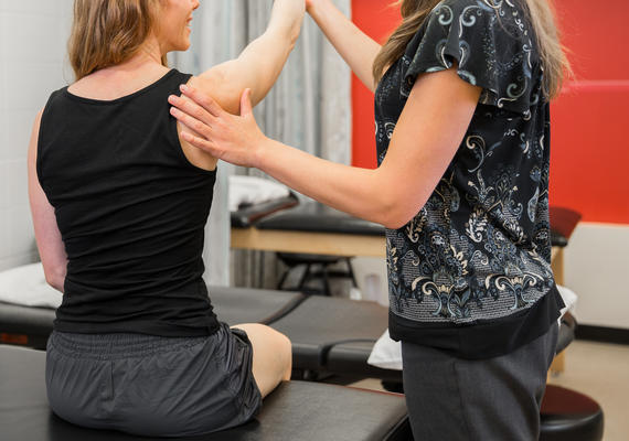 health practitioner taking a patient through shoulder assessment